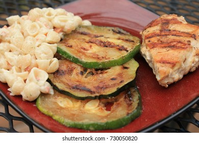Close-up of Grilled Chicken with Zucchini Slices and Pasta on Plate on Metal Table Outside