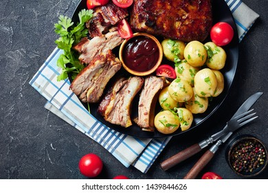 close-up of grilled pork ribs topped with barbecue sauce served with tomatoes and boiled hot potatoes served on a black plate on a concrete table, view from above, flatlay,