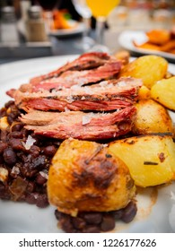 Closeup of a grilled pork roast with roasted potatoes