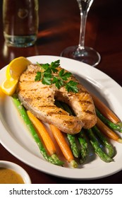 Closeup of grilled salmon steak garnished with baby carrots and asparagus. White wine and delicious sauce. Instagram style.