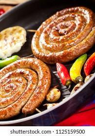 Closeup of grilled spiral sausages with vegetables and spices in a pan