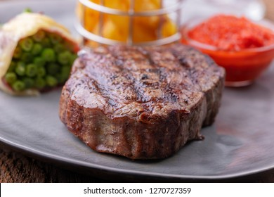 closeup of grilled steak with french fries