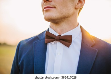 Closeup of groom with bow tie, shirt and jacket in sunset. Shallow focus, back light, lens flare.