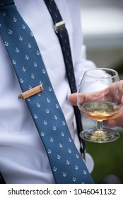 Close-up of a groom enjoying a glass of scotch before his wedding ceremony
