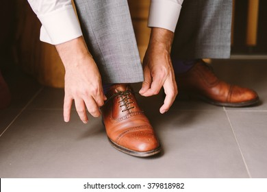 a close-up of a groom tie the shoelaces of the brown leather shoes