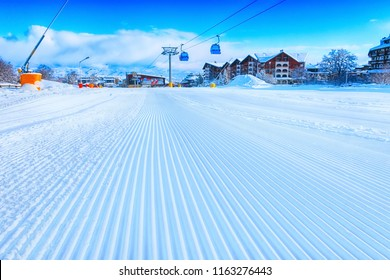Close-up groomed snow at Bansko resort, Bulgaria panorama with ski slope and cable car lift