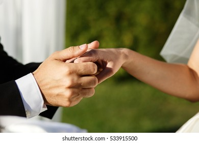 Close-up of groom's armds holding tender bride's fingers