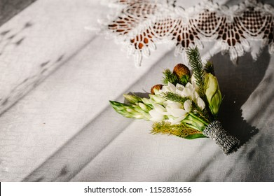 Close-up the groom's buttonhole white flowers and green and greenery lying on the table. Bride's Preparations. Wedding Morning concept.