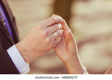 A closeup of groom's hand rouching bride's fingers delicately