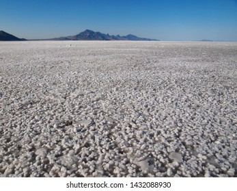 Closeup at ground level, looking out across the vast  Bonneville Salt Flats, with mountains far in the distance, the horizon appears to curve againsta blue late day sky.