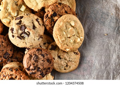 Closeup of a group of assorted cookies. Chocolate chip, oatmeal raisin, white chocolate pn parchment paper with copy space