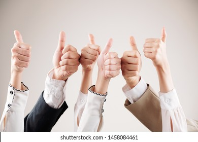 Close-up of group of business people raising their arms up and showing thumbs up isolated on white background