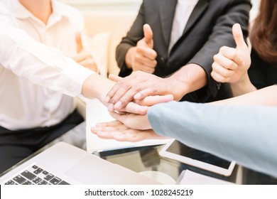 Close-up group of business together as a team by overlapping hands to symbolize their cooperation in working successfull.