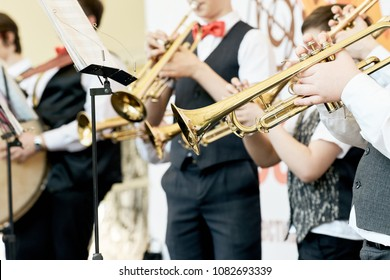 Closeup of a group of children playing musical instruments in an orchestra.