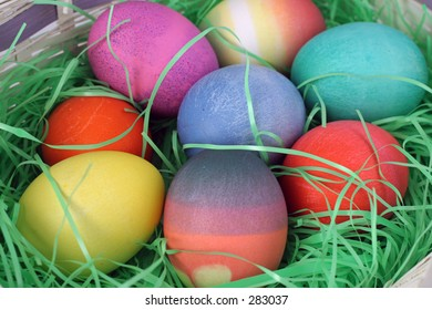 A closeup of a group of colorful Easter eggs nestled in grass.