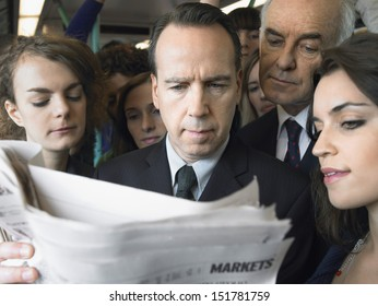 Closeup of a group of commuters reading newspaper in train