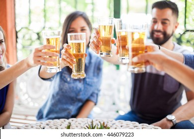 Closeup of a group of good friends spending time together and making a toast with some cold beers outdoors