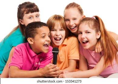 Close-up of a group of happy exited diversity looking kids, boys and girls, singing together sitting on the coach in living room