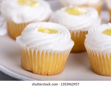 Closeup of a group of lemon cupcakes with white icing on a plate