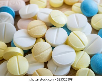 Closeup group of medicine pill on wood background, pharmaceutical theme (Selective focus)