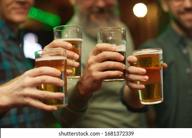 Close-up of group of men holding glasses of beer and celebrating the holiday