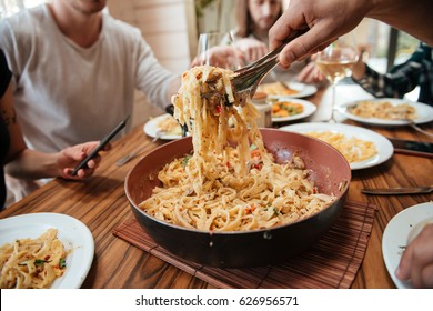 Closeup of group of people eating pasta on the kitchen at home