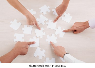 Close-up of group of people pointing at pieces of puzzles and collecting them together in team