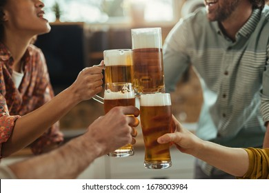 Close-up of group of people toasting with beer at home party.