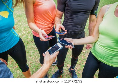 closeup of a group of sportsmen and sportswomen comparing their results on their mobile phones with sport apps outdoor in the city park