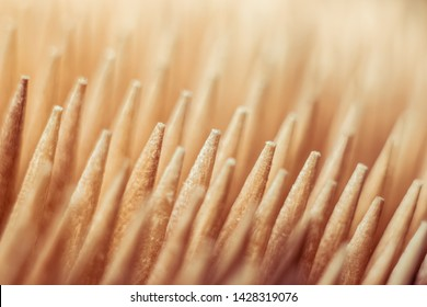 Close-up of a group of wooden toothpicks pointed and sharp, brown, forming a pattern or texture
