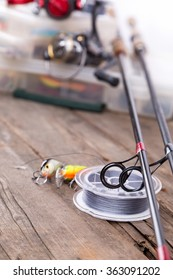 closeup guide rings on graphite rods and watted cord with blur background from fishing tackles and lure boxes.