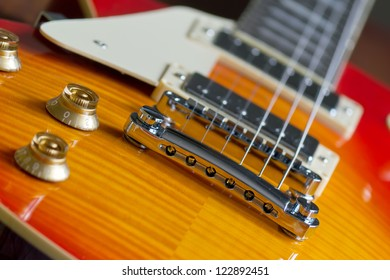 closeup of a guitar bridge with control knobs