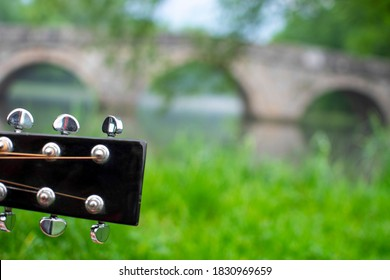 Closeup of guitar headstock with blured Roman bridge in background. Famous touristic place in Sarajevo, Bosnia