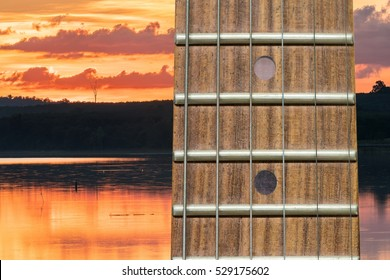 Close-up the Guitar neck aligned, Rosewood fingerboard neck on Beautiful sunset over silhouette mountain skyline with orange sky background