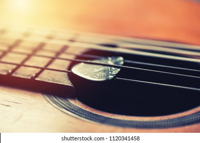 Closeup guitar pick on an old classical guitar. A guitar pick is a plectrum used for guitars.