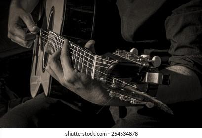 A closeup of a guitar player strumming.