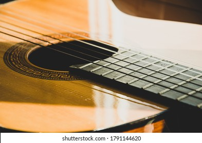 Close-up of guitar strings in sunlight. Guitar fretboard part, acoustic six-string wooden guitar, stringed musical instrument.