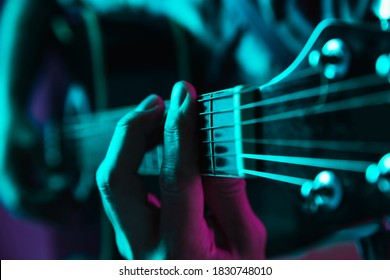 Close-up of guitarist hand playing guitar, macro. Concept of advertising, hobby, music, festival, entertainment. Person improvising inspired. Copyspace to insert image or text. Colorful neon lighted.