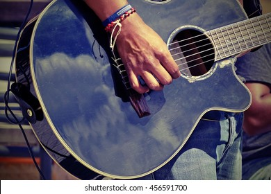 Close-up Of  Guitarist Male Hand And Fingers Who Touches String On The Black Acoustic Six String Guitar. Street Musical Band Play Latin Music