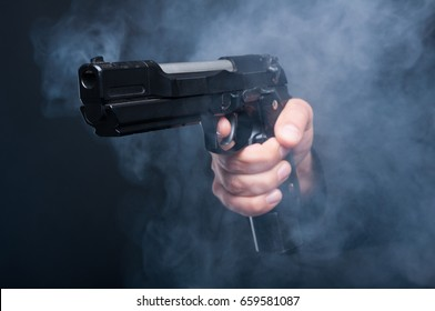 Closeup of gun in boss mafia hand on black background