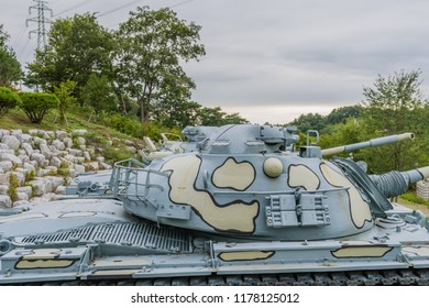 Closeup of gun turret on military tank with camouflage paint on display in public park near Nonsan, South Korea.