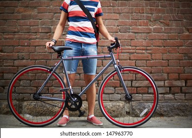 Close-up of guy with bicycle against brick wall