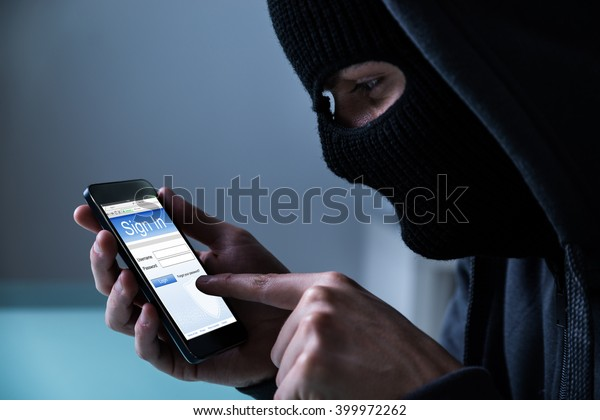 Close-up Of Hacker Using Smart Phone To Steal Data In Office