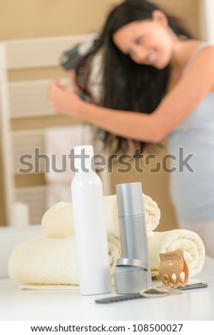 Close-up hair products in bathroom brunette woman drying hair