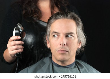 Close-up of a hair stylist preparing to use clipper having removed bulk length.