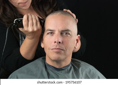 Close-up of a hair stylist using clippers to shave her Clients head.