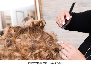 Closeup hairdresser coiffeur makes hairstyle