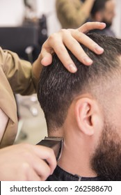 Close-up of hairdresser cutting hair of a male with hair clipper on back of the head  in hairdressing salon.