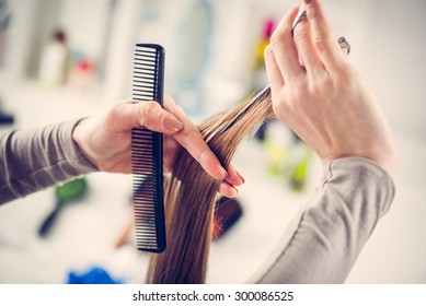 Close-up of a hairdresser cutting the hair of a woman.