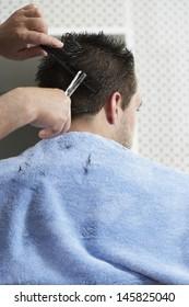 Closeup of hairdresser cutting man's hair in barber shop